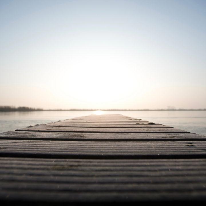 Steiger in een meer met lage zon