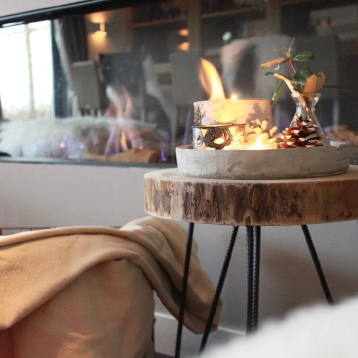 Haard met brandende kaarsen op een tafel ervoor
