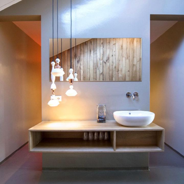 Wastafel op houten design wasmeubel met tros witte hanglampen