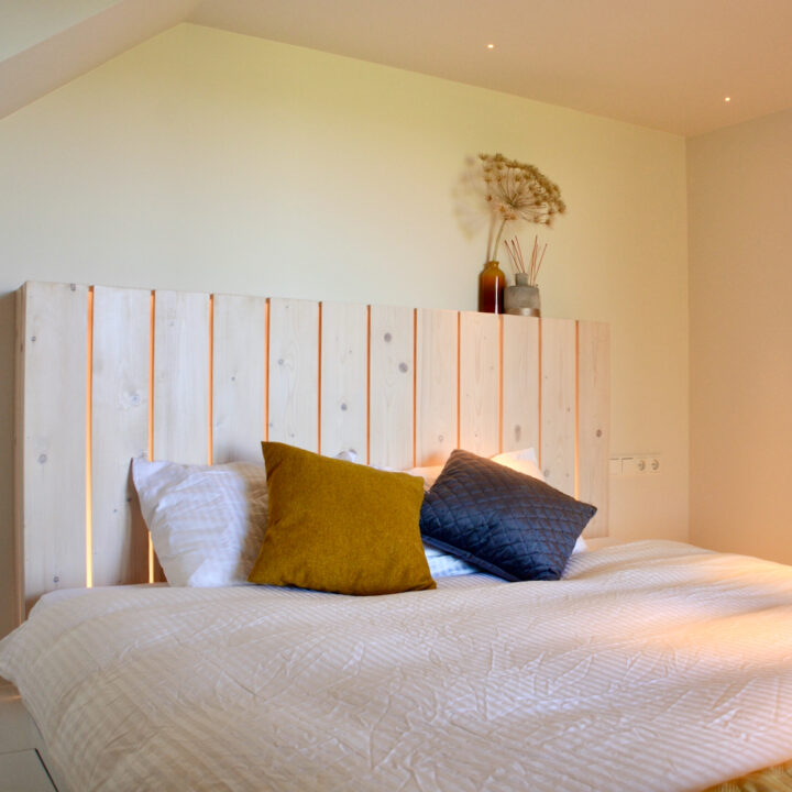 Tweepersoons bed met houten achterwand