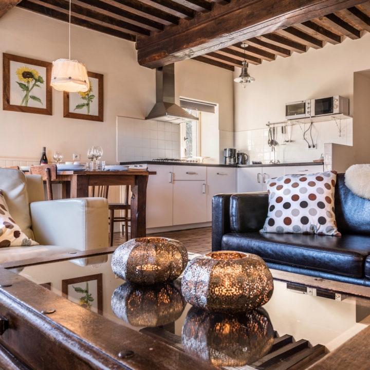 Salontafel met twee waxinelichtjes, bank met kussens en doorkijkje naar witte keuken