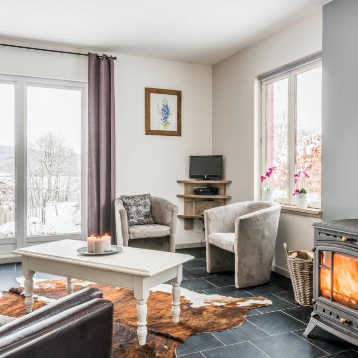 Brandende kachel, zithoek met twee grijze fauteuils, grote ramen