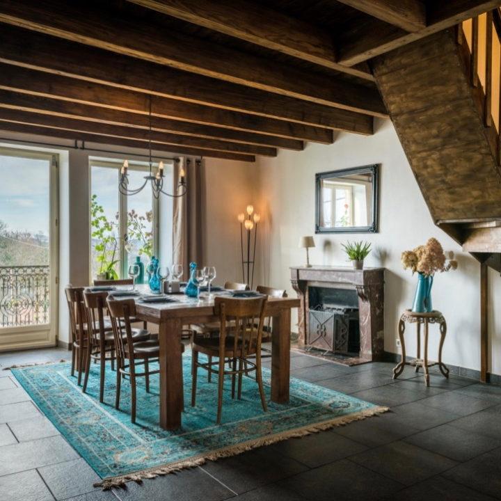 Eethoek met houten tafels en stoelen, blauw vloerkleed en houten balken