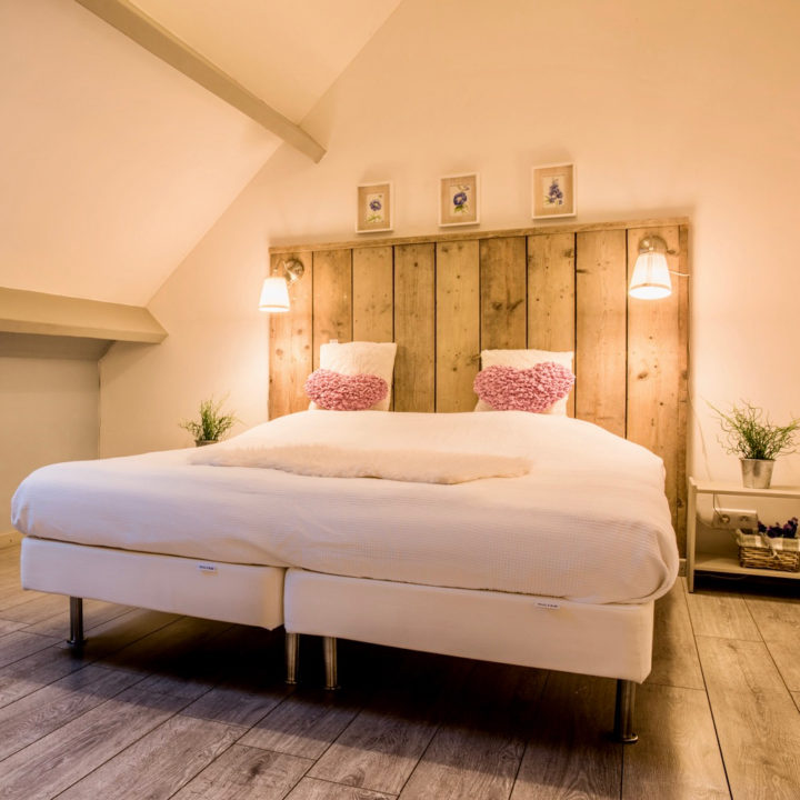 Tweepersoons bed met wit beddengoed, hartjes kussens en steigerhouten achterwand