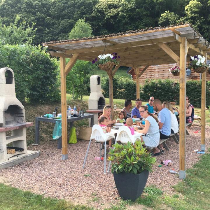 Lange tafel onder een overkapping, etende gasten