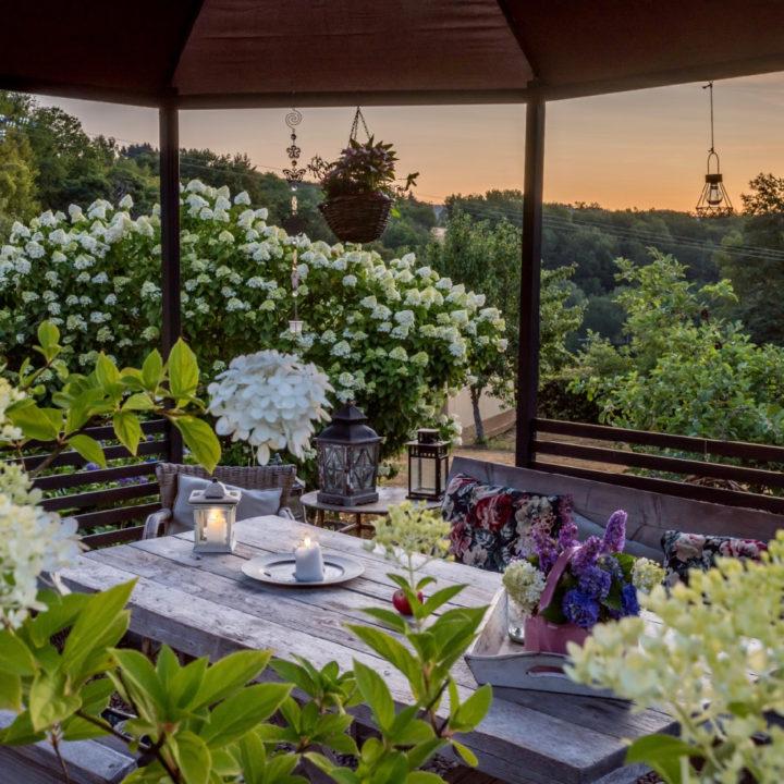Overdekt terras met veel bloemen en planten bij zonsondergang