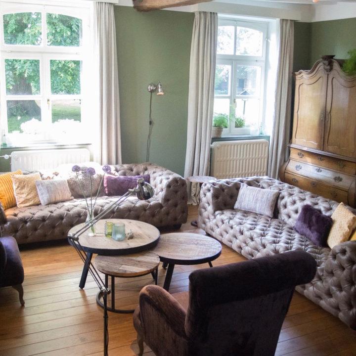 De woonkamer van de kasteelboerderij met 2 banken en 2 stoelen