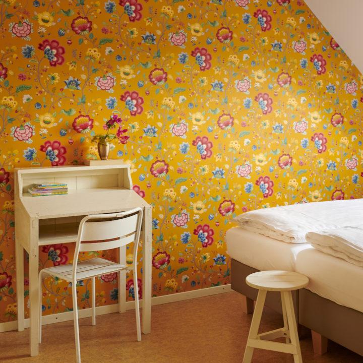 Slaapkamer in vakantiehuis met hip behang, okergeel met bloemen