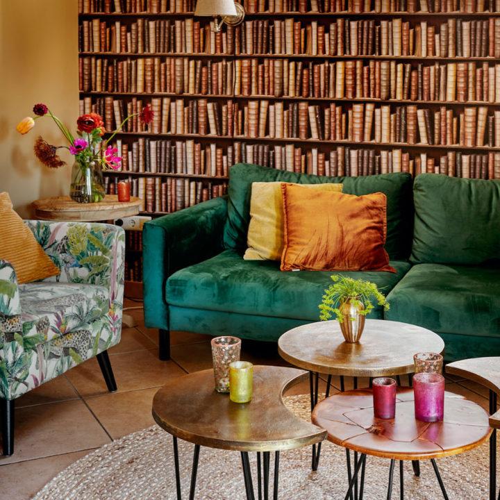 Zithoek met behang van een boekenkast