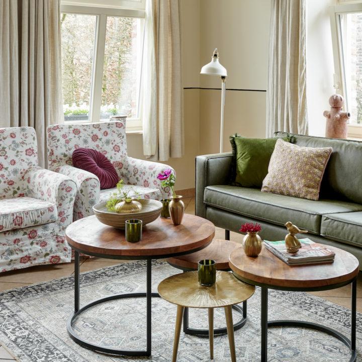 Landelijk ingerichte woonkamer met donkergroene bank en gebloemde fauteuils