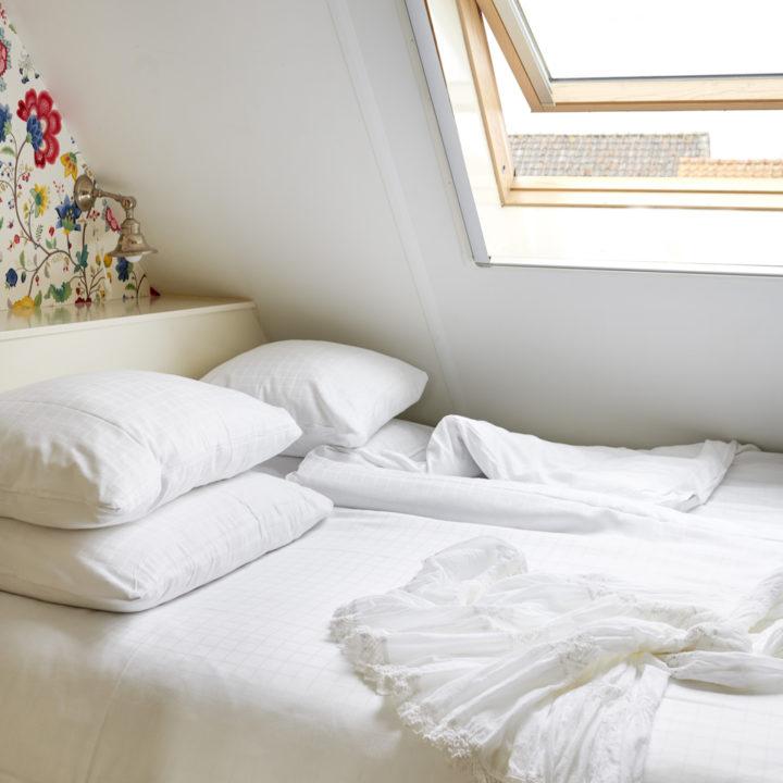 Tweepersoons bed onder een dakraam