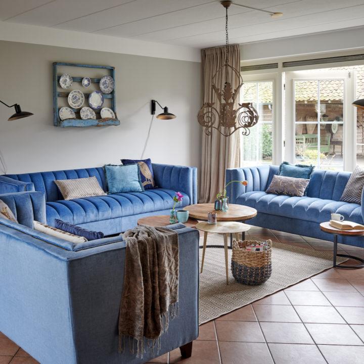 Woonkamer met blauwe banken en brocante accessoires