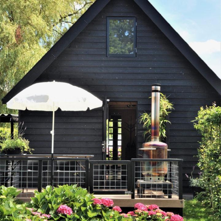 Zwart houten huis met terras en buitenkachel
