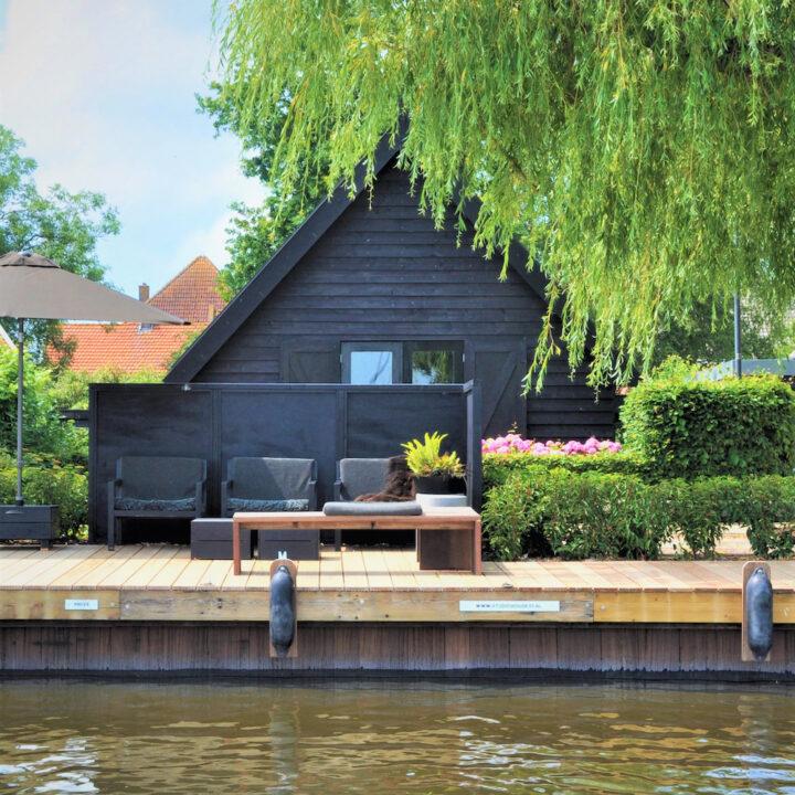 Zwart vakantiehuis met terras aan het water