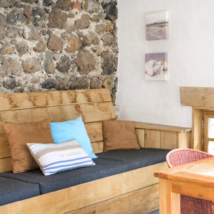 Loungeplek met steigerhouten bank in een vakantiehuis in de Auvergne