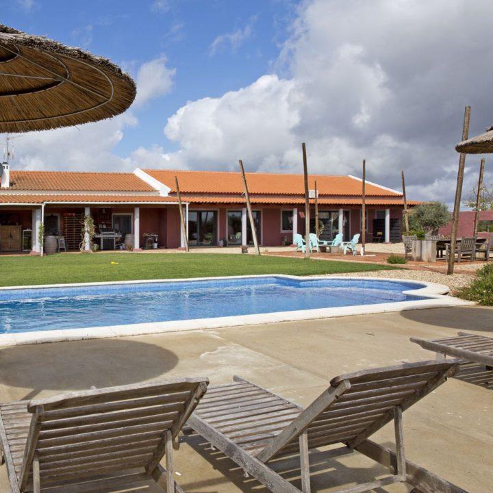 Ligstoelen aan de rand van het zwembad bij Vila Valmonte