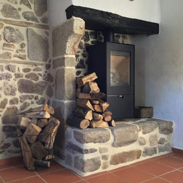Zwarte houtkachel met houtblokken