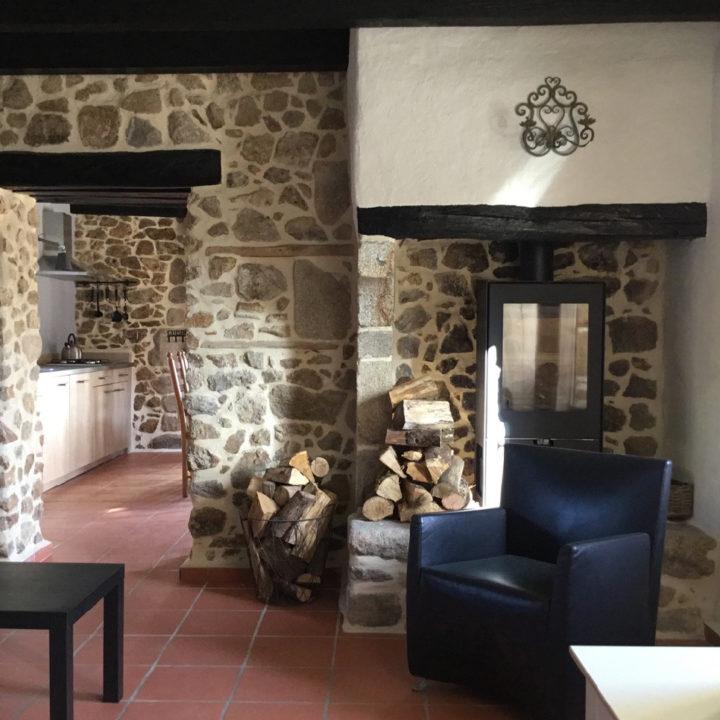 Woonkamer met zwarte fauteuil en haard met houtblokken