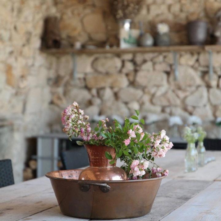 Tafel met een koperen schaal en bloemetjes in een vaas