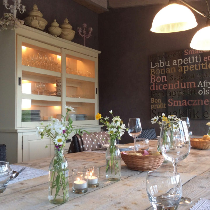 Lange tafel met wijnglazen, bloemetjes en mandjes brood