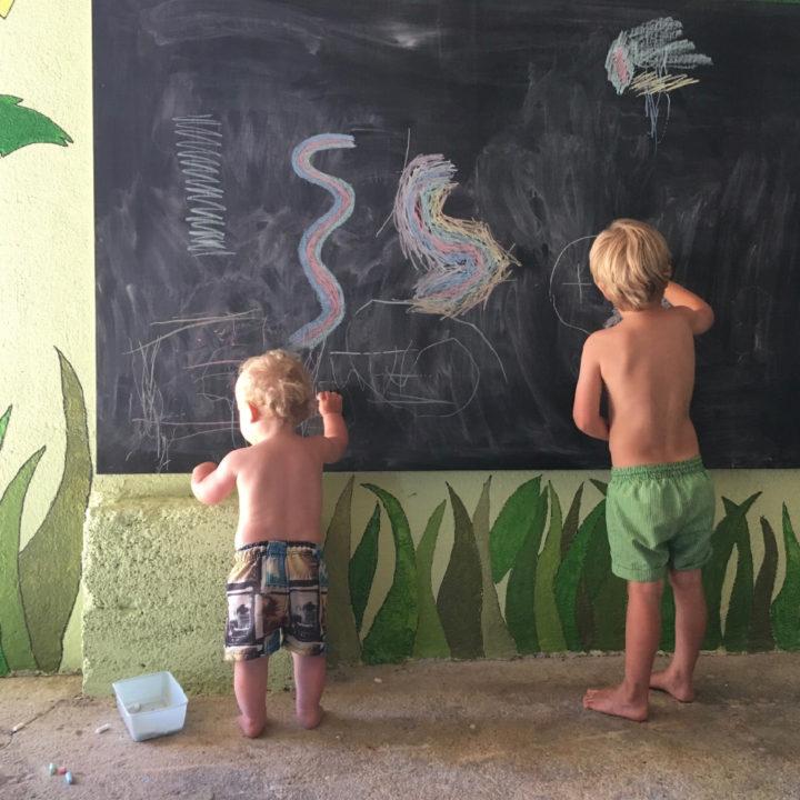 Twee kinderen in zwembad kleuren op een krijtbord