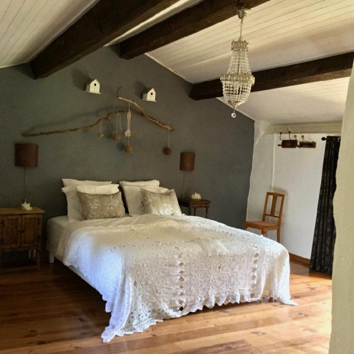 Slaapkamer met een twee persoons bed met wit beddengoed en gehaakte sprei