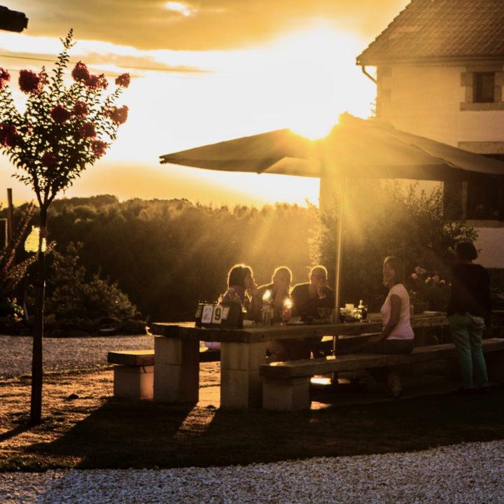 Lange tuintafel met banken, een parasol en vakantiegangers in de avondzon