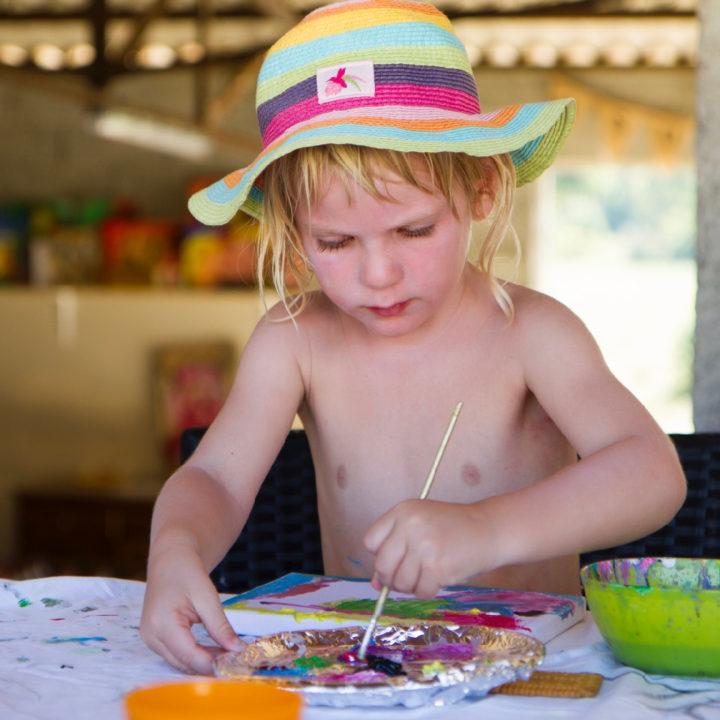 Workshop schilderen, een kindje met zonnehoedje is fanatiek aan het schilderen