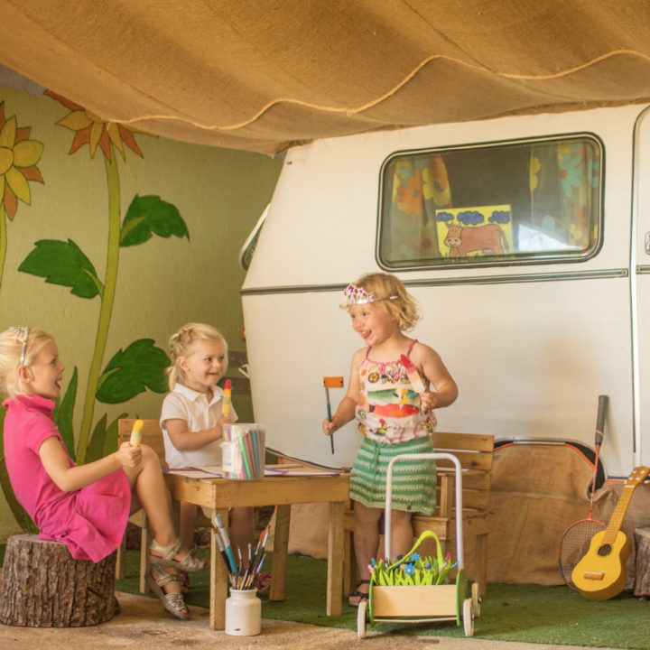 Een witte caravan, omgetoverd tot speelplek met daarvoor drie meisjes aan het spelen