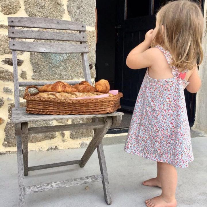 Een meisje bij een stoeltje met daarop een mandje met croissants en stokbrood