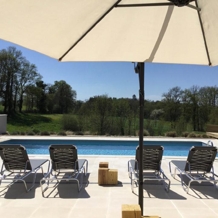 Een zwembad met een witte parasol en ligstoelen, zicht op groene heuvels