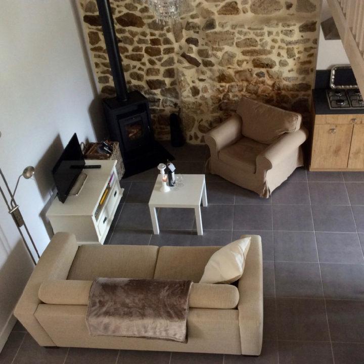 Een woonkamer met twee beige banken en een wit tafeltje, van bovenaf gezien