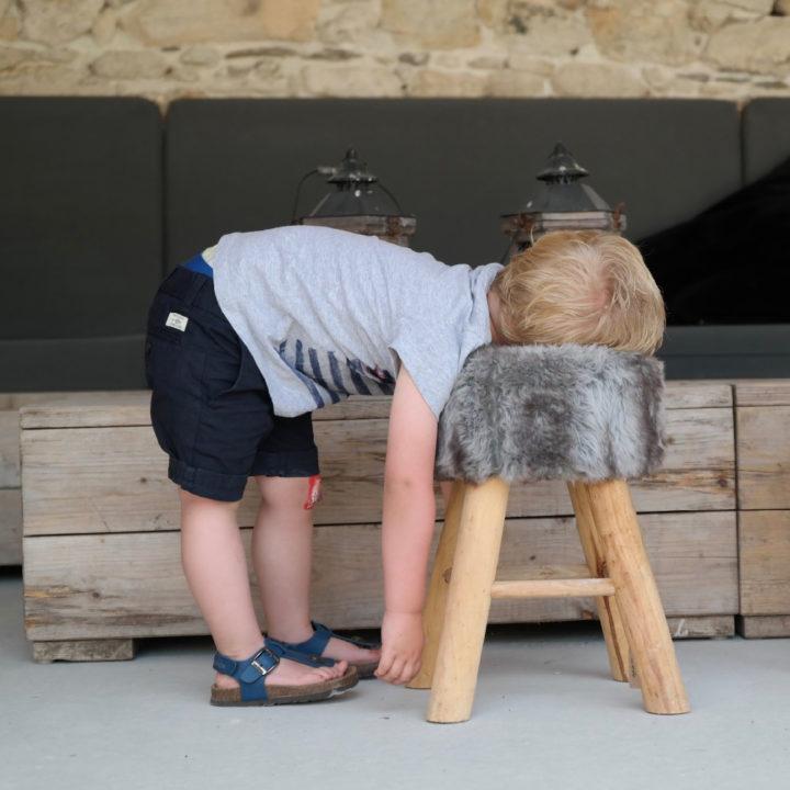 Een jongetje hangt op een krukje met bont, uitgeput