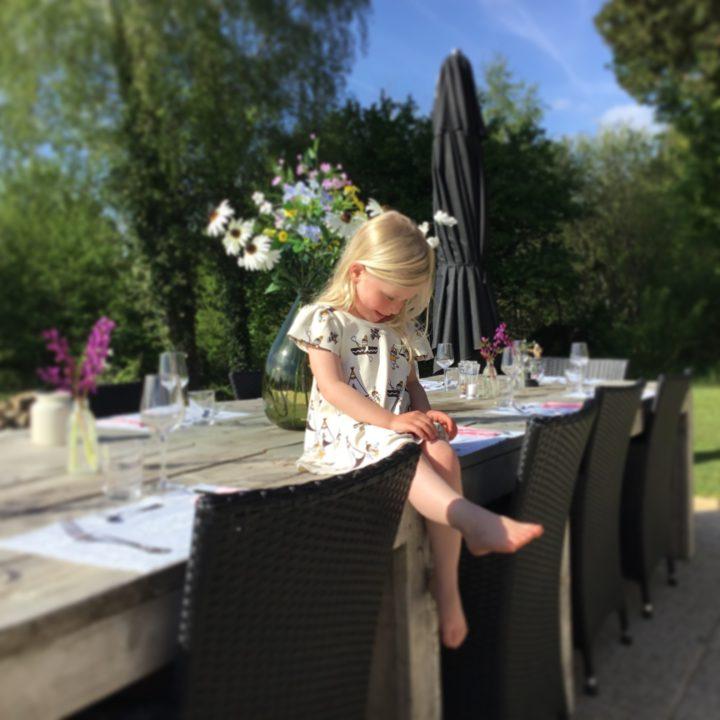 Een meisje in een zomerjurkje, op een gedekte tafel