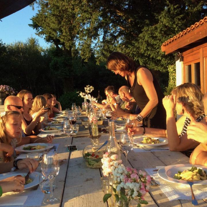 Lange tafel met vakantiegasten, in de avondzon