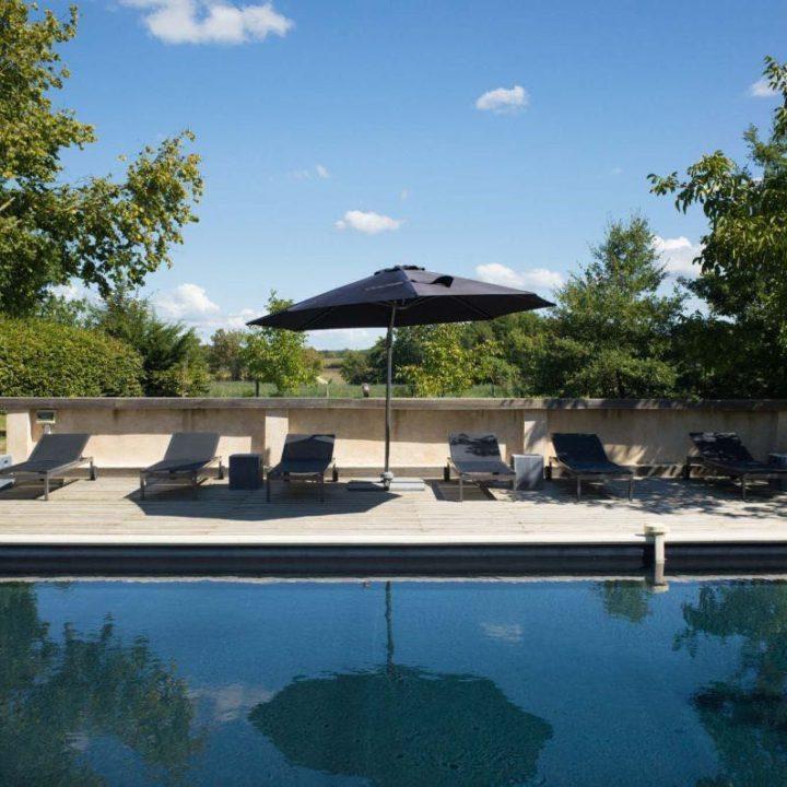 Zwembad met zwarte parasol en ligstoelen