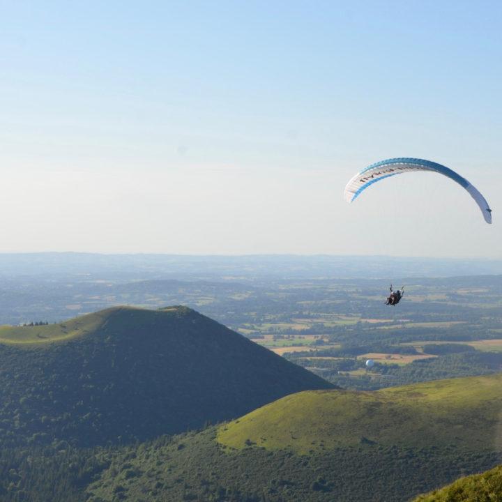 Groen heuvelland met een paraglider erboven