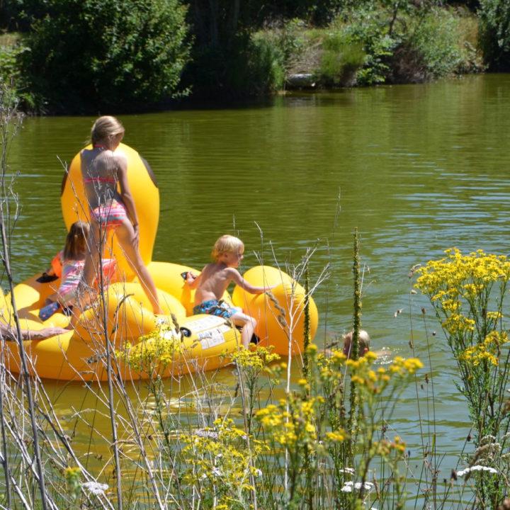 Een gele rubberboot op een meertje, met spelende kinderen