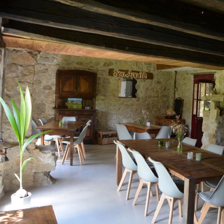 Houten tafels met grijze kuipstoelen voor de gasten