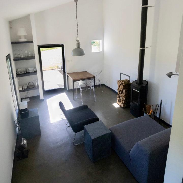 Interieur van een design vakantiehuis. Met houtkachel, antraciet kleurige bank en witte muren