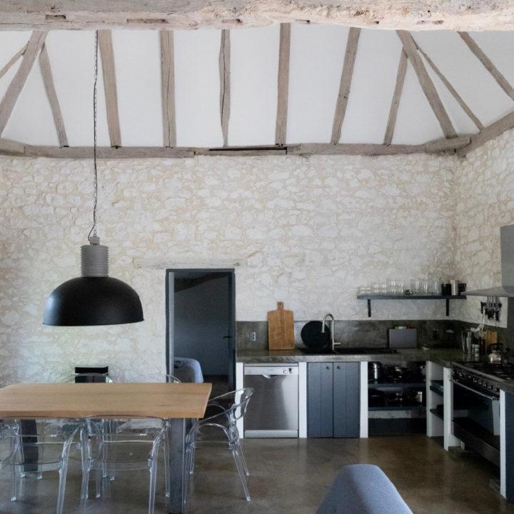 Een grote open ruimte met keuken en eettafel