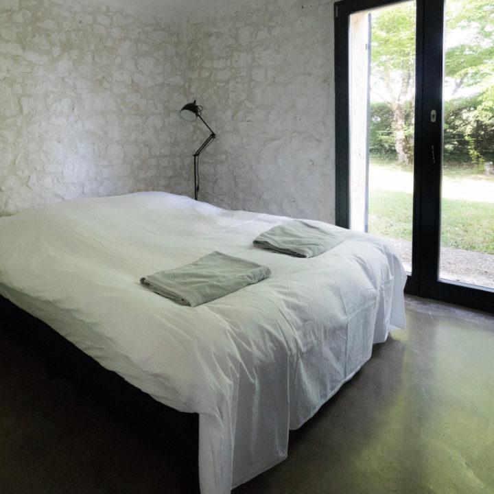 Tweepersoons bed met bedlinnen en handdoeken