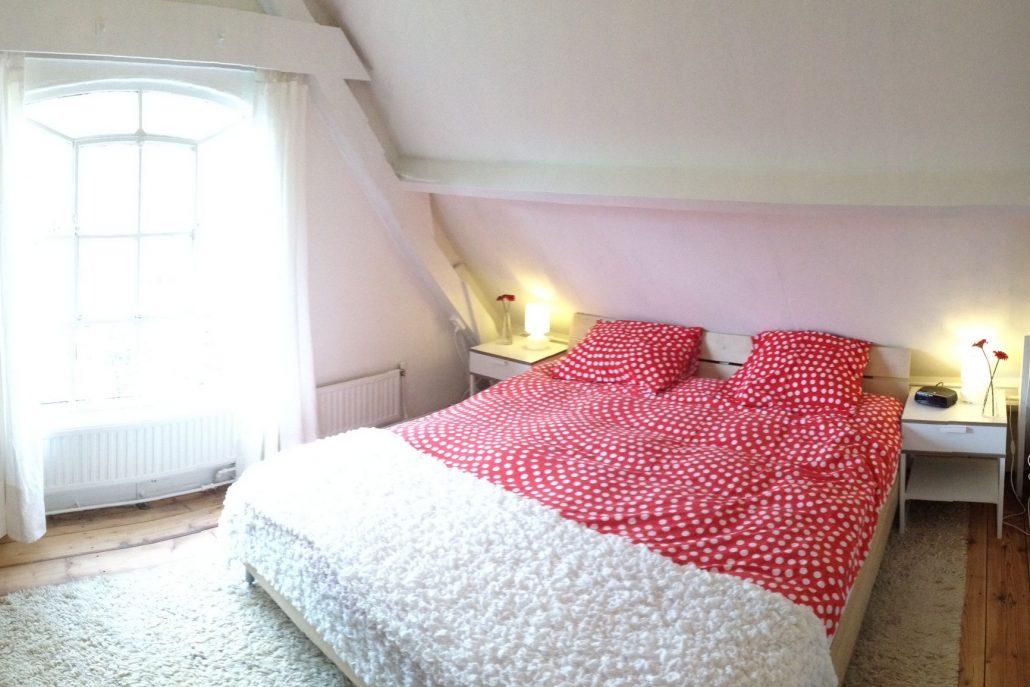 Tweepersoons slaapkamer met bed met roodwit dekbed