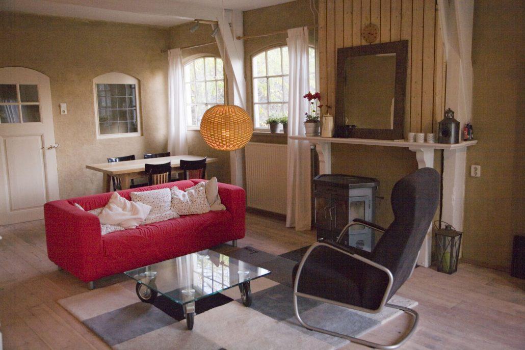 Woonkamer met houtkachel, rode bank en fauteuil