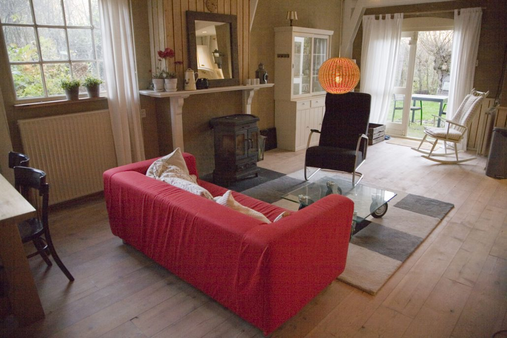 Overzicht woonkamer met rode bank, kachel en openslaande deuren