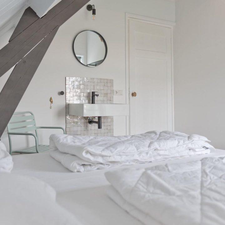 Dekbedden op bed in de slaapkamer van het vakantiehuis in Domburg