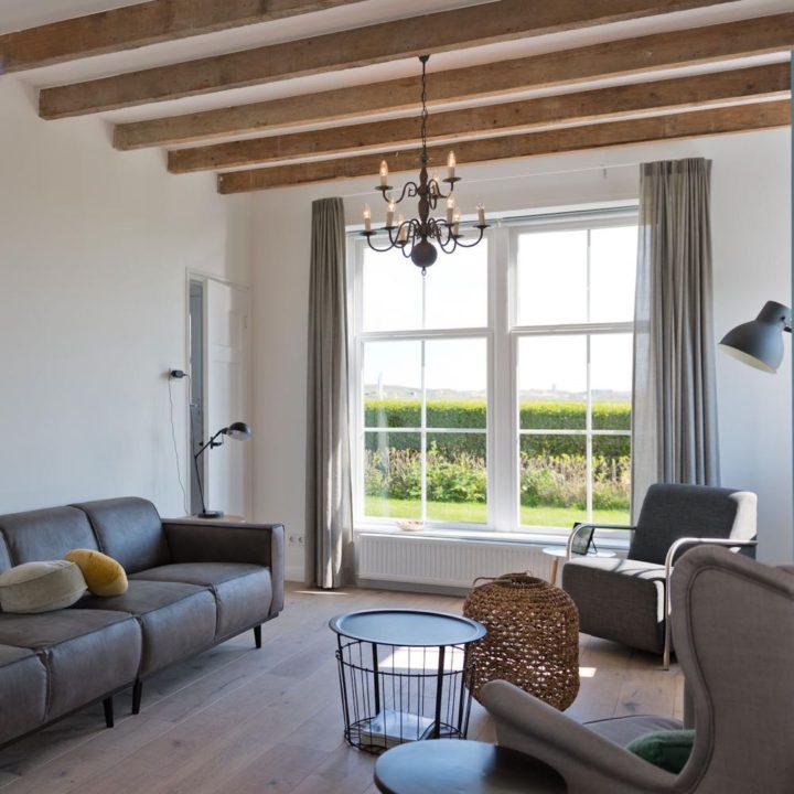 Moderne woonkamer met grote ramen met zicht op de duinen en weilanden