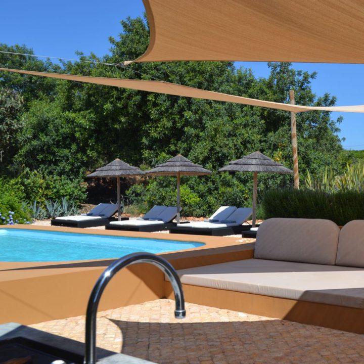 Zwembad in de tuin van een vakantiehuis, met ligstoelen en een loungebank