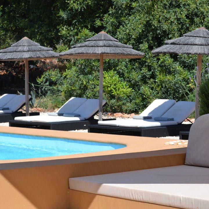 Zwembad met ligstoelen en rieten parasols