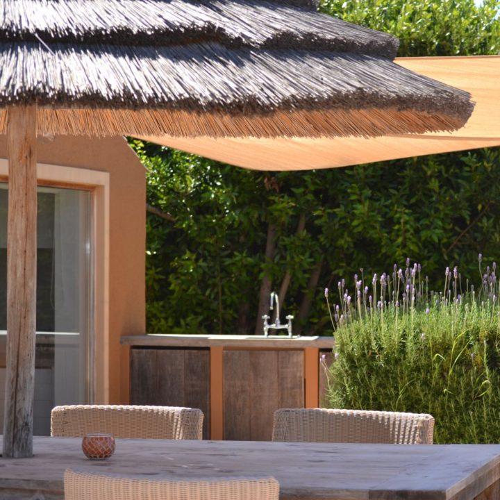 Eethoek in de tuin, met buitenkeuken en rieten parasol